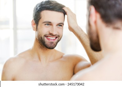 Starting new day with smile. Handsome young man touching his hair with hand and smiling while standing in front of the mirror