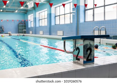 Starting platform with number two is in swimming pool for children groups. Kids practice with instructor