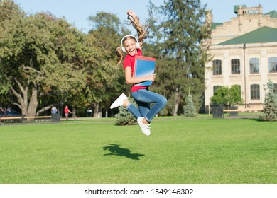 Starting school in good mood. Happy schoolgirl jump to music on green grass. Active little child in headphones hold school books. Back to school. School holidays. Summer vacation. Primary education.