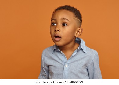 Startled astonished black dark skinned schoolboy posing in studio with mouth wide openend staring in front of him with fright, shock, can't believe his own eyes. Astonishment and surprise concept