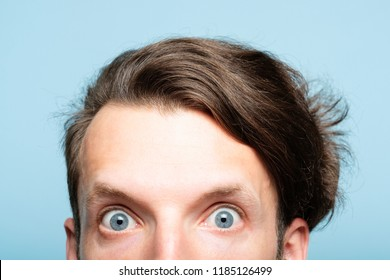 startled eccentric whimsical man with crazy look closeup. head of a young brunet guy peeking out from the bottom of blue background. emotion and facial expression concept.