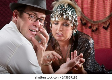 Startled male with gypsy palm reader holding his hand