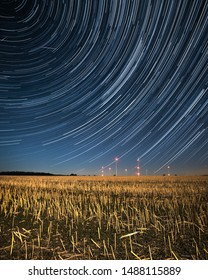 Startrails above a field with wind turbines, illuminated by the light of the moon
