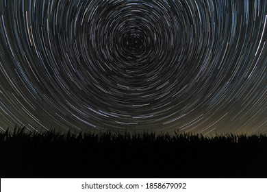 Startrails at night, above a field.