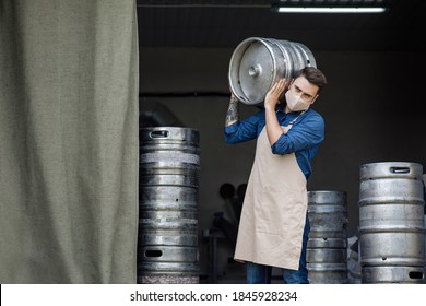 Startup of beer business and work at factory during COVID-19 epidemic. Young handsome male brewer or worker in protective mask and apron holds big metal keg at brewery factory warehouse, free space