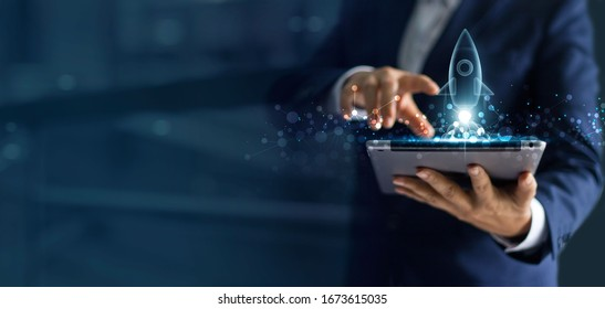 Startup business concept, Businessman holding tablet and icon transparent rocket is launching and soar flying out from screen with network connection on dark blue modern background.