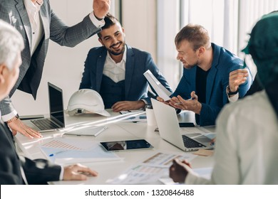 startup business, creative multiethnic business people of different age and races gather in meeting room in white modern office interior, vivously discussing, celebrating success