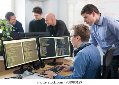 Startup business and entrepreneurship. Young software developers team brainstorming and programming on desktop computer in startup company share office space.