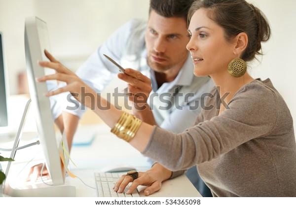 デスクトップで共同作業を行う、起業中のビジネスパートナー