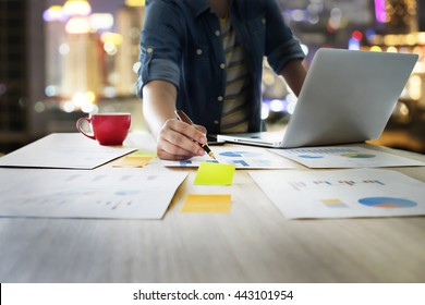 Startup business people using laptop and summery business chart to analyze marketing situation. Working people doing overtime at night in office.