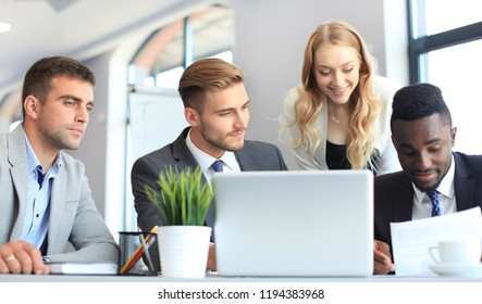 Startup business team on meeting in modern bright office interior and working on laptop.