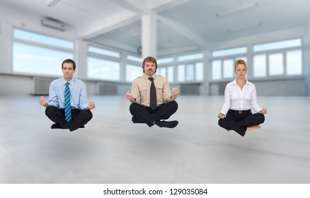 Startup business - young business people meditating in empty office space