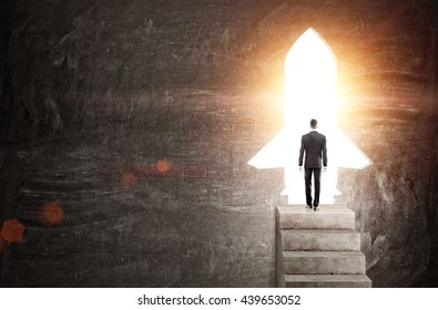 Startup concept with businessman standing on concrete stairs against rocket shaped door with bright light. Chalkboard background