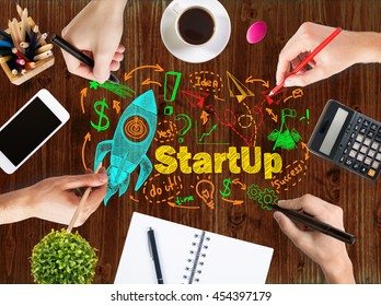 Startup concept with businesspeople hands drawing space ship sketch on wooden office desk with blank smartphone, coffee cup, stationery and other items
