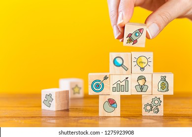 Startup concepts with business strategy symbols on wooden cubes.