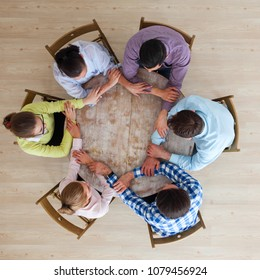 Startup diversity teamwork brainstorming meeting concept, people sitting around the table and holding hands, unity, togetherness