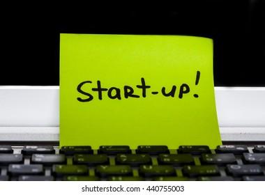 Start-up! A green sticky note on a notebook