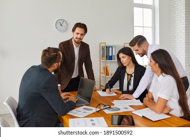 Startup group meeting around office desk in creative workspace. Start-up leader listening to teammates' suggestions, talking, discussing budget issues and work needs. Sales team analyzing results