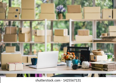 Startup home office interior with parcel box on the shelves, laptop, coffee cup and barcode scanner on the table, work space no peple background for sme startup online shopping concept