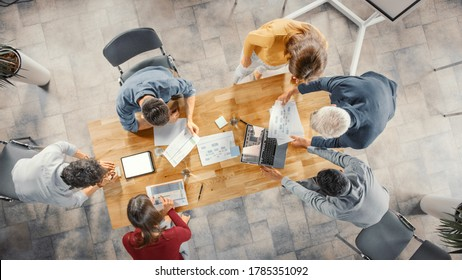 Startup Meeting Room: Team of Entrepreneurs Standing Around Conference Table Have Discussions, Solve Problems, Use Digital Tablet, Laptop, Share Documents with Statistics, Charts. Top View Shot