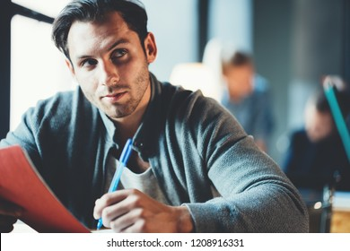 Startup and millenial business concept. Portrait of thinking manager working with note pad in office