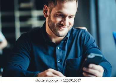 Startup and millenial business concept. Portrait of manager in office smiling and using mobile phone