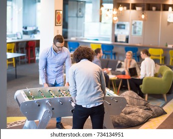 Startup Office People Enjoying Table Soccer Game During their Free Time at the creative Workplace