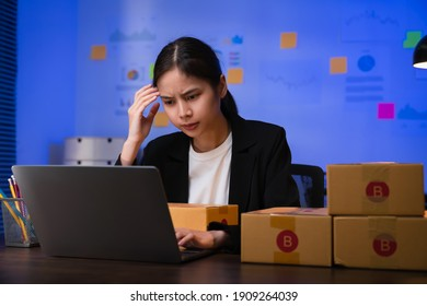 Startup small business concept, young woman owner hands touch on the forehead have a headache because of stress, and checking online order on digital laptop with packing on the box at home office.