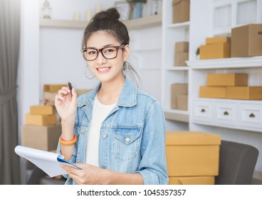 Startup small business entrepreneur SME, asian woman writing clipboard. Portrait young Asian small business owner at warehouse home office, online marketing packing delivery, SME e-commerce concept