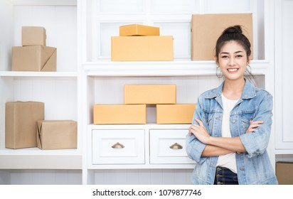 Startup small business entrepreneur SME, portrait freelance asian woman standing with boxes in home office, online marketing packing delivery, SME e-commerce telemarketing warehouse concept