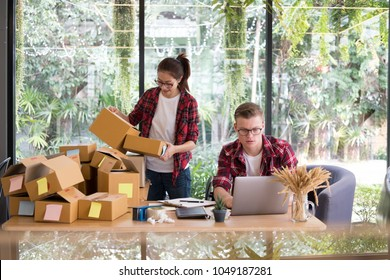 startup small business owner working with computer at workplace. freelance man & woman seller check product order, packing goods for delivery to customer.  Online selling, e-commerce, shipping concept