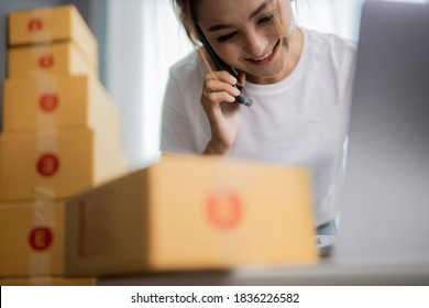 Startup small business SME, Entrepreneur owner using smartphone or tablet taking receive and checking online purchase shopping order to preparing pack product box.