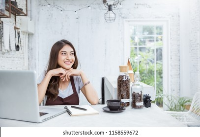 Startup successful entrepreneur small business owner SME asian woman sit look up in coffee shop or restaurant. Portrait of young girl successful barista cafe owner woman sme concept with copy space