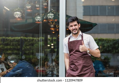 Startup successful small business owner caucasian man stand in his coffee shop or restaurant. Portrait of young caucasian man successful barista cafe owner concept