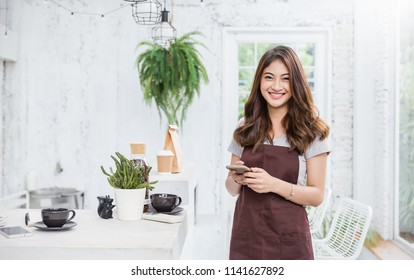 Startup successful small business owner woman sme beauty girl standing in coffee shop or restaurant. Portrait of young asian tan woman barista cafe owner. SME entrepreneur business concept banner
