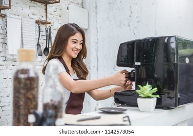 Startup successful small business owner sme woman beauty girl using coffee machine in coffee shop restaurant. Portrait of young asian tan woman barista cafe owner. SME entrepreneur business concept