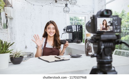 Startup successful small business owner sme beauty vlogger girl video online marketing with camera in cafe. Portrait young asian tan woman barista cafe owner. SME entrepreneur blogger business concept