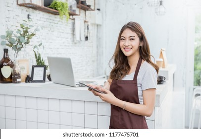 Startup successful small business owner sme beauty girl standing with tablet smartphone in coffee shop restaurant. Portrait of asian tan woman barista cafe owner. SME entrepreneur business concept