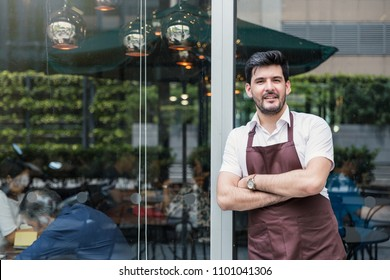 Startup successful sme small business owner man walking in his coffee shop or restaurant. Portrait of young smile caucasian man successful barista cafe local owner