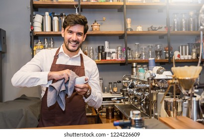Startup successful sme small business entrepreneur owner man cleaning cup in his coffee shop or restaurant. Portrait of young caucasian man successful barista cafe owner indoors.