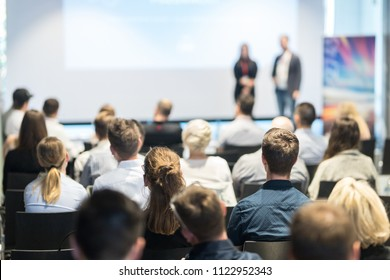 Startup team giving a pitch deck presentation in conference hall at business event. Audience at the conference hall. Business and Entrepreneurship concept. Focus on unrecognizable people in audience.