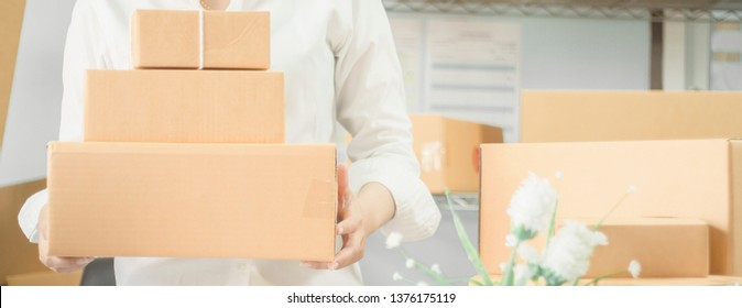 Startup working at workplace business owner smile happily preparing to deliver packed into cardboard deliver customers,Concept online business trading and e commerce shipping,banner horizontal for web