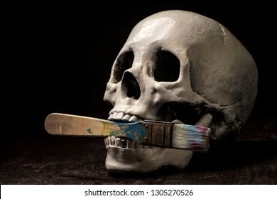 Starving artist human skull eating or holding paintbrush in mouth