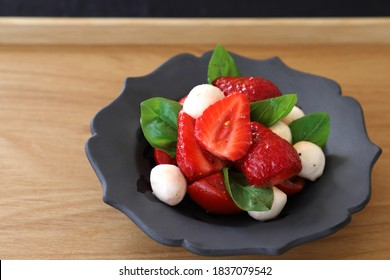 Starwberry and tomato caprese salad in black bowl.