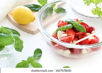 Starwberry and tomato caprese salad in glass bowl