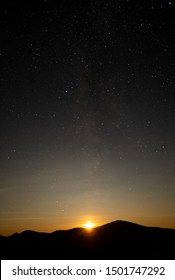 Stary night sky with the moon going down over dark mountain landscape - Shutterstock ID 1501747292