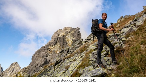 Stary Smokovec, Slovakia - September 12, 2019: Hiker with a backpack and trekking poles in the mountains.