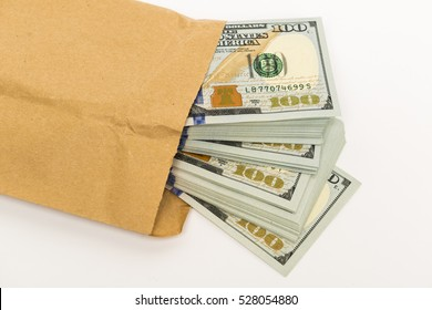 Stash of money in hundred dollar cash banknotes coming out of envelope