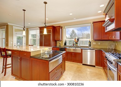 State of the art kitchen with stone tile floor and a tall island.