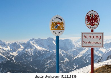 """State boundary between Germany and Austria on top of Alpine mountain ridge. Signboards with the coat of arms of free state Bavaria and Tyrol and words """"Warning: National Border""""."""